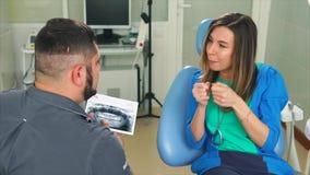 Μια νέα γυναίκα λέει στον οδοντίατρο ποια δόντια την ενοχλούν, εξετάζει την ακτίνα X φιλμ μικρού μήκους