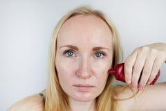 Μια νέα γυναίκα βάζει μια μάσκα πηκτωμάτων στο πρόσωπό της Προσοχή για το ελαιούχο, δέρμα προβλήματος στοκ φωτογραφία