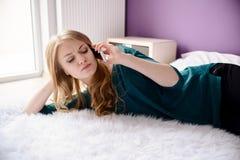 Μια νέα γυναίκα βρίσκεται στο κρεβάτι και την ομιλία στο τηλέφωνο κυττάρων Στοκ Εικόνα