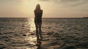 Μια νέα γυναίκα εισάγει χαριτωμένα το νερό στο ηλιοβασίλεμα της ημέρας σε ένα kiteboarding κλίμα απόθεμα βίντεο
