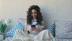 Μια νέα γυναίκα επικοινωνεί με έναν φίλο στο κινητό τηλέφωνό της μετά από να ξυπνήσει απόθεμα βίντεο