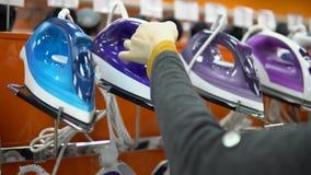 Μια νέα γυναίκα επιλέγει έναν σίδηρο σε ένα κατάστημα εγχώριων συσκευών απόθεμα βίντεο