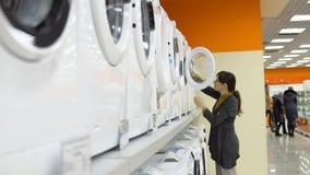 Μια νέα γυναίκα επιλέγει ένα πλυντήριο σε ένα κατάστημα εγχώριων συσκευών φιλμ μικρού μήκους