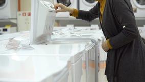 Μια νέα γυναίκα επιλέγει ένα πλυντήριο σε ένα κατάστημα εγχώριων συσκευών απόθεμα βίντεο