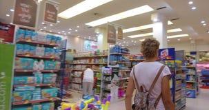 Μια νέα γυναίκα επιλέγει και αγοράζει τα προϊόντα και τα αγαθά σε μια υπεραγορά απόθεμα βίντεο