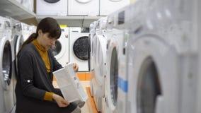 Μια νέα γυναίκα επιλέγει μια ξηρότερη μηχανή σε ένα κατάστημα εγχώριων συσκευών φιλμ μικρού μήκους