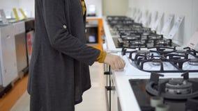 Μια νέα γυναίκα επιλέγει μια σόμπα αερίου σε ένα κατάστημα εγχώριων συσκευών απόθεμα βίντεο