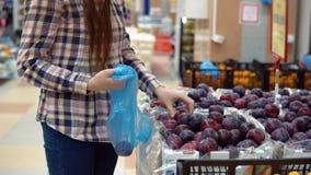 Μια νέα γυναίκα επιλέγει τα δαμάσκηνα σε μια υπεραγορά απόθεμα βίντεο