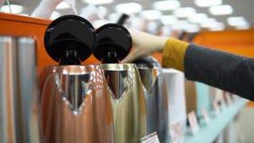 Μια νέα γυναίκα επιλέγει teapot σε ένα κατάστημα εγχώριων συσκευών απόθεμα βίντεο