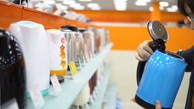 Μια νέα γυναίκα επιλέγει teapot σε ένα κατάστημα εγχώριων συσκευών φιλμ μικρού μήκους