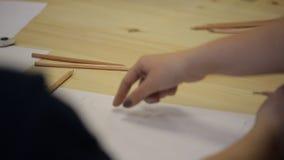 Μια νέα γυναίκα επισύρει την προσοχή με το μολύβι σε χαρτί, το χέρι του καλλιτέχνη επιδεικνύει πόσο σωστά φιλμ μικρού μήκους
