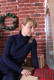 Μια νέα γυναίκα κάθεται κοντά σε ένα παράθυρο Χριστούγεννα Στοκ Φωτογραφία