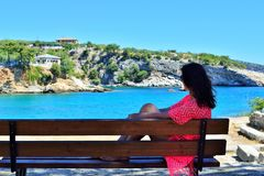 Μια νέα γυναίκα κάθεται σε έναν πάγκο στοκ φωτογραφίες