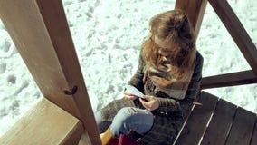 Μια νέα γυναίκα κάθεται σε μια ξύλινη βεράντα, σιωπηλά σχετικά με το αεροπλάνο εγγράφου origami με τα δάχτυλά της και την τοποθέτ Στοκ εικόνα με δικαίωμα ελεύθερης χρήσης