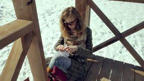 Μια νέα γυναίκα κάθεται σε μια ξύλινη βεράντα, σιωπηλά σχετικά με το αεροπλάνο εγγράφου origami με τα δάχτυλά της και την τοποθέτ Στοκ εικόνες με δικαίωμα ελεύθερης χρήσης