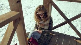 Μια νέα γυναίκα κάθεται σε μια ξύλινη βεράντα, σιωπηλά σχετικά με το αεροπλάνο εγγράφου origami με τα δάχτυλά της και την τοποθέτ Στοκ Εικόνα