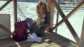 Μια νέα γυναίκα κάθεται σε μια ξύλινη βεράντα, σιωπηλά σχετικά με το αεροπλάνο εγγράφου origami με τα δάχτυλά της και την τοποθέτ Στοκ Εικόνες