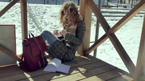 Μια νέα γυναίκα κάθεται σε μια ξύλινη βεράντα, σιωπηλά σχετικά με το αεροπλάνο εγγράφου origami με τα δάχτυλά της και την τοποθέτ Στοκ Φωτογραφίες