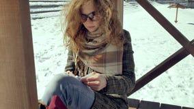 Μια νέα γυναίκα κάθεται σε μια ξύλινη βεράντα, σιωπηλά σχετικά με το αεροπλάνο εγγράφου origami με τα δάχτυλά της και την τοποθέτ Στοκ φωτογραφία με δικαίωμα ελεύθερης χρήσης