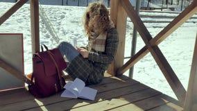 Μια νέα γυναίκα κάθεται σε μια ξύλινη βεράντα, σιωπηλά σχετικά με το αεροπλάνο εγγράφου origami με τα δάχτυλά της και την τοποθέτ Στοκ Φωτογραφία