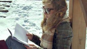 Μια νέα γυναίκα κάθεται σε μια ξύλινη βεράντα, σιωπηλά σχετικά με το αεροπλάνο εγγράφου origami με τα δάχτυλά της και την τοποθέτ Στοκ φωτογραφίες με δικαίωμα ελεύθερης χρήσης