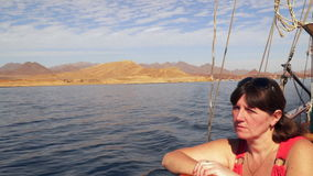 Μια νέα γυναίκα κάθεται στη γέφυρα ενός γιοτ απόθεμα βίντεο