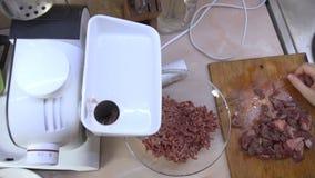 Μια νέα γυναίκα κάνει το επίγειο κρέας χρησιμοποιώντας ένα μηχανή κοπής κιμά στην κουζίνα της απόθεμα βίντεο