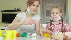 Μια νέα γυναίκα και ένα κορίτσι φορμάρουν τα δόντια τους από το plasticine, παρεμβάλλουν τα δόντια τους σε ένα σαγόνι παιχνιδιών, απόθεμα βίντεο