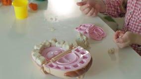 Μια νέα γυναίκα και ένα κορίτσι φορμάρουν τα δόντια τους από το plasticine, παρεμβάλλουν τα δόντια τους σε ένα σαγόνι παιχνιδιών, φιλμ μικρού μήκους
