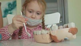 Μια νέα γυναίκα και ένα κορίτσι φορμάρουν τα δόντια τους από το plasticine, παρεμβάλλουν τα δόντια τους στο σαγόνι του παιχνιδιού φιλμ μικρού μήκους