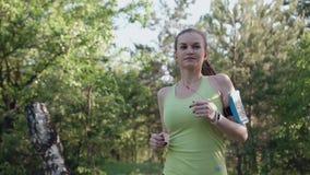 Μια νέα γυναίκα με έναν λεπτό αριθμό τρέχει στο δάσος στο ηλιοβασίλεμα Υγιής τρόπος ζωής, αθλητής κοριτσιών που κάνει το τρέξιμο απόθεμα βίντεο