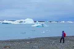 Μια νέα γυναίκα με ένα κόκκινο σακίδιο πλάτης στέκεται σε ένα κλίμα των μπλε παγόβουνων Λιμνοθάλασσα πάγου στην Ισλανδία στοκ φωτογραφίες