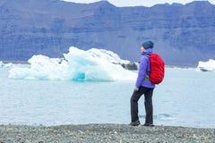 Μια νέα γυναίκα με ένα κόκκινο σακίδιο πλάτης στέκεται σε ένα κλίμα των μπλε παγόβουνων Λιμνοθάλασσα πάγου στην Ισλανδία στοκ εικόνες