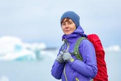 Μια νέα γυναίκα με ένα κόκκινο σακίδιο πλάτης στέκεται σε ένα κλίμα των μπλε παγόβουνων Λιμνοθάλασσα πάγου στην Ισλανδία στοκ φωτογραφίες με δικαίωμα ελεύθερης χρήσης