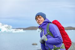 Μια νέα γυναίκα με ένα κόκκινο σακίδιο πλάτης στέκεται σε ένα κλίμα των μπλε παγόβουνων Λιμνοθάλασσα πάγου στην Ισλανδία στοκ εικόνα