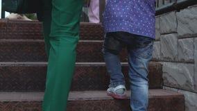 Μια νέα γυναίκα με μια μικρή κόρη αναρριχείται στα σκαλοπάτια φιλμ μικρού μήκους