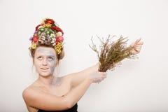 Μια νέα γυναίκα με τα λουλούδια σε ετοιμότητα το κεφάλι και της Εικόνα άνοιξη με τα λουλούδια Άτομο με ζωηρόχρωμες εγκαταστάσεις  στοκ φωτογραφία