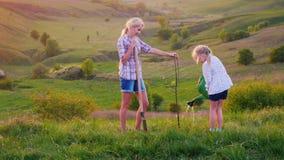 Μια νέα γυναίκα με την κόρη της 6 χρονών φυτεύει ένα δέντρο Το κορίτσι ποτίζει το σπορόφυτο από το πότισμα μπορεί, έπειτα απόθεμα βίντεο