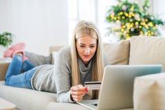 Μια νέα γυναίκα με την πιστωτική κάρτα και lap-top στο σπίτι στο χρόνο Χριστουγέννων στοκ φωτογραφίες