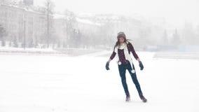 Μια νέα γυναίκα με τον άσπρο πάγο μαντίλι που κάνει πατινάζ έξω βαριές χιονοπτώσεις στοκ φωτογραφία με δικαίωμα ελεύθερης χρήσης