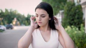 Μια νέα γυναίκα με τους σκοτεινούς περίπατους τρίχας κάτω από την οδό το καλοκαίρι, η κυρία κοιτάζει σκεπτικά γύρω, είναι ντυμένη απόθεμα βίντεο