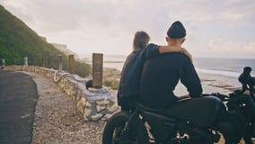 Μια νέα γυναίκα με το φίλο της, ο αναβάτης και η μοτοσικλέτα του θαυμάζουν μαζί τη θαυμάσια άποψη γύρω, βουνό και φιλμ μικρού μήκους