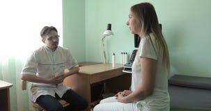 Μια νέα γυναίκα μιλά σε έναν γιατρό στην κλινική απόθεμα βίντεο