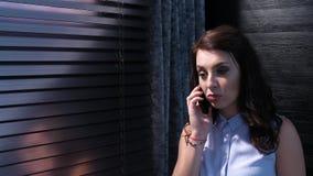 Μια νέα γυναίκα μιλά στο κινητό τηλέφωνό της και στέλνει τα μηνύματα SMS Είναι στο παράθυρο με τους κλειστούς τυφλούς 01 απόθεμα βίντεο