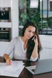 Μια νέα γυναίκα ξοδεύει το χρόνο στο σπίτι, στην κουζίνα και στο roo Στοκ Εικόνες