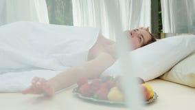 Μια νέα γυναίκα ξυπνά σε έναν αργόσχολο, που καλύπτεται με τις κουρτίνες, κοντά σε την ένα πιάτο των φρούτων Πανέμορφες ρομαντικέ απόθεμα βίντεο