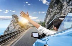 Μια νέα γυναίκα οδηγεί με το αυτοκίνητο στη θάλασσα και κυματίζει το χέρι της από ένα μπλε μετατρέψιμο αυτοκίνητο Διακοπές στην π στοκ εικόνα