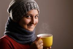 Μια νέα γυναίκα πίνει ένα φλυτζάνι του καυτού τσαγιού στο χειμώνα που απομονώνεται στο άσπρο υπόβαθρο στοκ φωτογραφίες