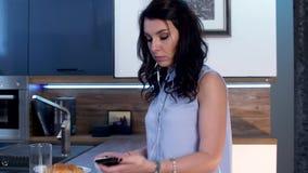 Μια νέα γυναίκα πίνει τον καφέ και στέλνει sms στο τηλέφωνο 01 απόθεμα βίντεο