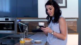 Μια νέα γυναίκα πίνει τον καφέ και στέλνει sms στο τηλέφωνο 02 απόθεμα βίντεο